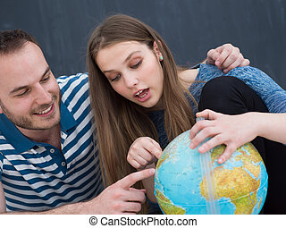 couple in casual clothing investigating globe - Young lovely...