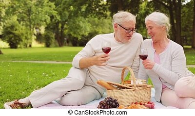 happy senior couple having picnic at summer park - old age,...