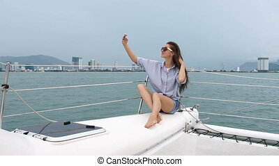 Woman making self-portrait photo while enjoying vacation on a boat