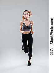 Full length portrait of a young woman in sportswear running...