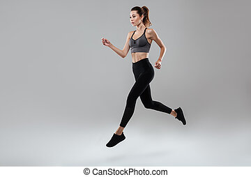 Side view full length portrait of a young fitness woman...