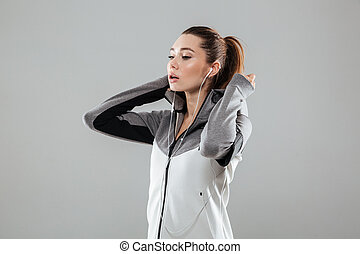 Young attractive fitness woman in earphones putting on her...
