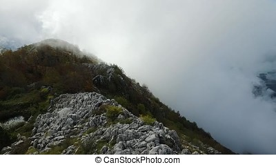 Woman stands on the cliff of the mountain. Footage. Aerial