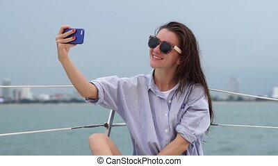 Woman takes self portrait photo while enjoying vacation on a...