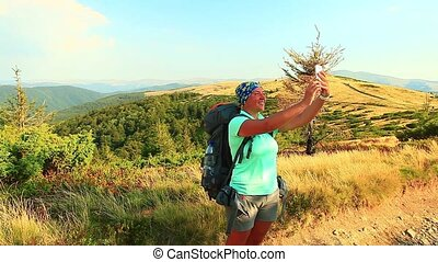 woman hikers taking selfie from top of the mountain with...