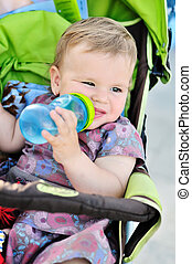 drinking baby girl - baby girl sitting in the stroller and...