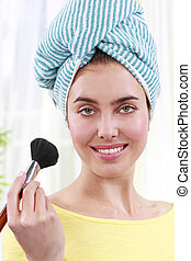 Woman with turban applies face powder - Woman with blue...