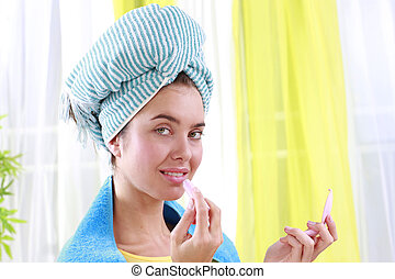 Woman with turban applies lipstick - Woman with a blue...