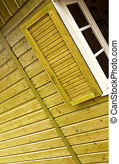 Window of a chalet - Window and shutter of a yellow wooden...