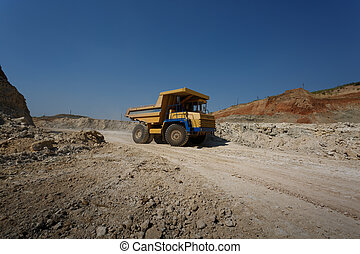 Side view of one yellow tip truck with a shadow on a natural background. Huge transporter in a sandy quarry.