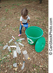 Child in blue latex gloves, throwing plastic bag into recycling bin. Land and rubbish on the background.