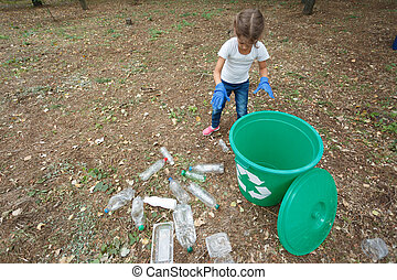 Child in blue latex gloves, throwing plastic bag into recycling bin. Land and rubbish on the background, outside photo,