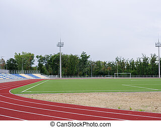 Green football field and red running track in the stadium. Running track on a stadium background. Sports concept. Copy space.