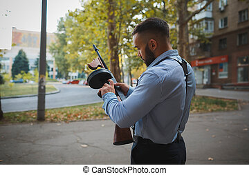 A confident handsome criminal holding a gun on an urban background. An elegant gangster in a blue shirt. Copy space.