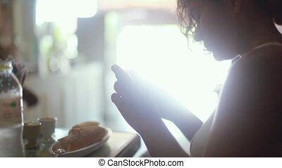 Young woman doing photos of breakfast on tablet and shares...
