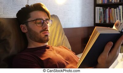 Young man lying in bed and reading a book - Young handsome...