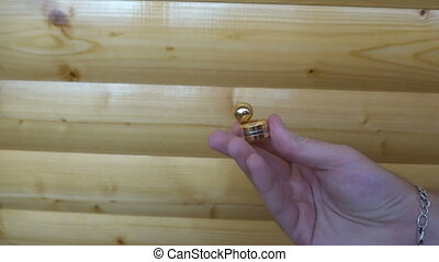 new gold fidget Orbiter,spinning in the hand of a young man on wooden background