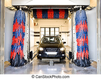Car wash - Black car with a male driver washing the car in a...
