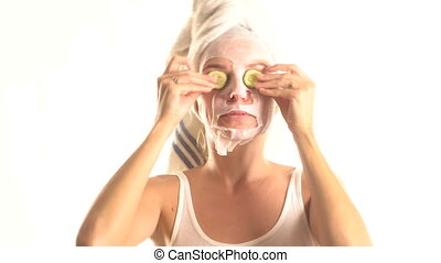 Woman with tissue cosmetic mask on her face