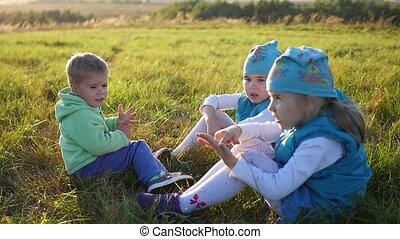 The children sit on the lawn in the Park. Laugh and smile. Children's holiday in the open air