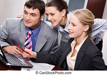 Three people - Portrait of three business people looking at...