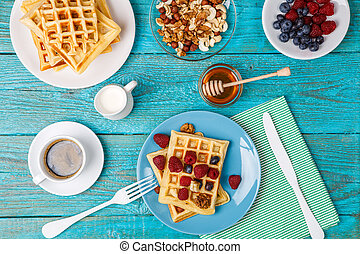 Homemade waffles with raspberries and blueberry, cup of...