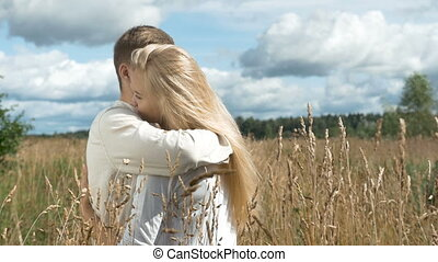 Young couple on date in wheat field.
