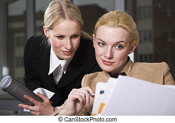 Getting an opinion - Two pretty women are reading an...
