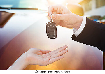 Salesman Handing Key To Woman By New Car - Cropped image of...