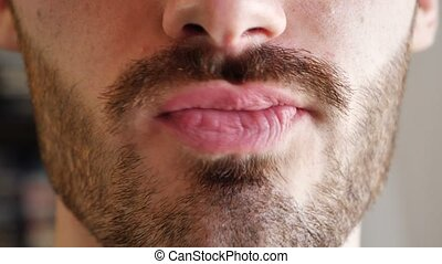 Close-up of man lips, while cleaning teeth with tongue -...
