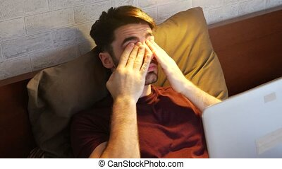 Young Man Doing Homework on Laptop in Bedroom - Attractive...