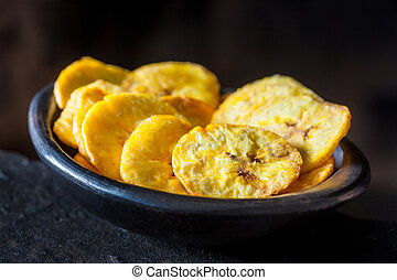 Plantain fried coins in a traditional black clay bowl on...