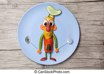 Chief made of vegetables and spoons on plate