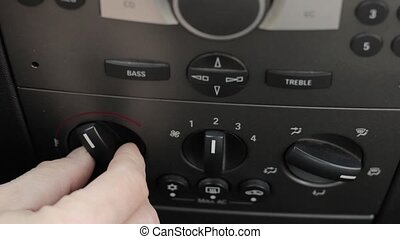 Man hand pushes the car climate control button. Regulator...
