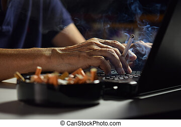 Man holding lit and smoking cigarette between fingers and...