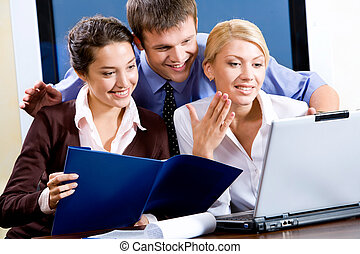 Business team of three people looking at monitor of laptop