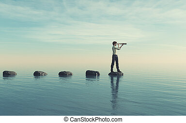 The young man sits on a large stone in the middle of the sea...