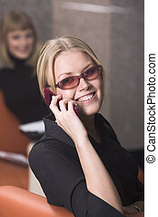 Talking by the cell phone - Smiling blond business lady in...