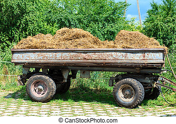 Tractor trailer full of hay outside the stable....