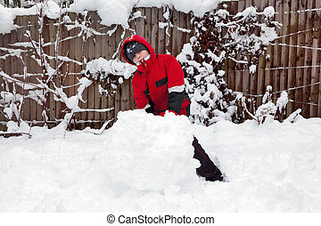 Young boy making a snowman - A young boy playing in the snow...