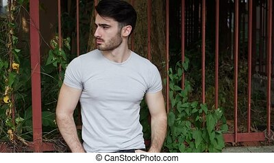Handsome young man outdoor looking around and at camera
