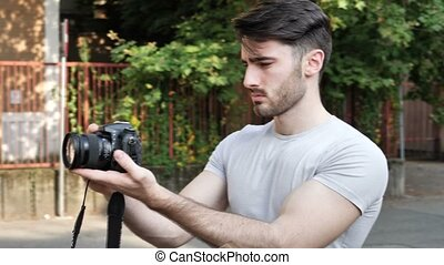 Young man posing with photo camera - Handsome man holding...