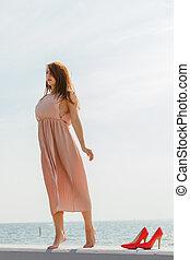 Woman wearing long light pink dress on jetty - Hobby,...
