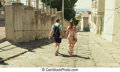 Young couple walking towards the sea in a Mediterranean town...