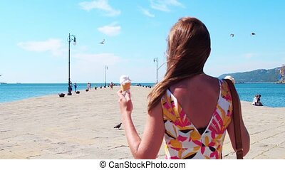 Young woman with ice cream cones walking on the sea pier