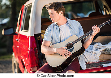 man playing guitar on car trunk - handsome young man playing...