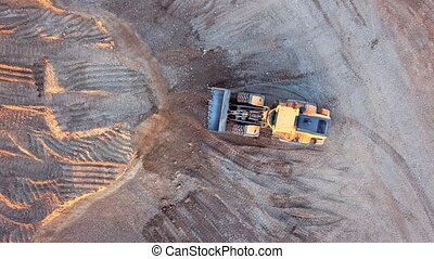 Bulldozer in action in open air quarry - Aerial view loading...