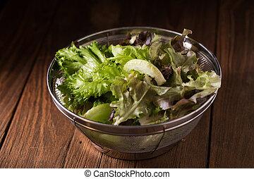 Crisphead lettuce in a bowl on wooden table. - Crisphead...