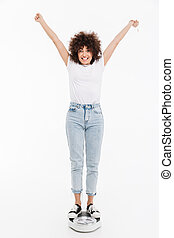 Happy cheerful woman standing on scales and holding her...