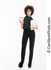 Smiling happy businesswoman in formal wear holding documents...